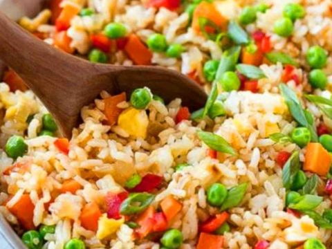 Vegetable Fried Rice In A Bowl With A Wooden Spoon In It On Table